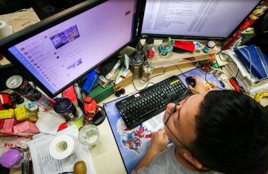 2018年10月11日,游戏公司余香科技,一个年轻人正在紧张地工作,桌子的一角摆满了各种饮料。
